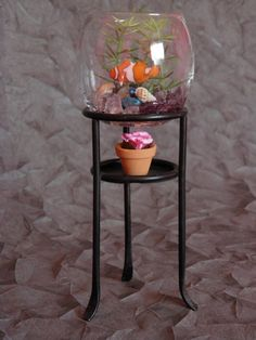 Votive candle holder repurposed as a fish tank for doll house.