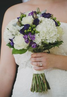 Purple and white bridal bouquet with white hydrangea, purple stock, white roses and green hypericum berries.