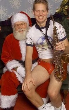 """How did this even come to happen? Who thought """"Wow, that would be an awesome Christmas photo""""? How uncomfortable is Santa? How will sax-boy ever explain this to anyone, ever?"""