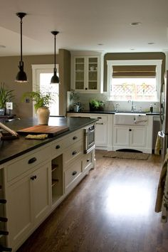 Farmhouse sink, cottage kitchen, dark countertops, wood floors and pendants