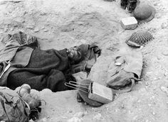 British soldier sleeping in a shallow foxhole in the Libyan desert, 1941.