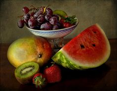 Vintage still life in chiaroscuro, tray with grapes and then mango, strawberries, kiwi and watermelon