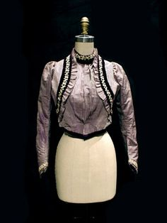 This violet and cream striped bodice is c. 1901. It is made from silk taffeta and appears to have a bolero over the top, but is constructed in one piece.