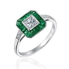 Platinum vintage style halo princess cut diamond and emerald ring featuring 1.54 tcw French carre cut emeralds, one 0.36 ct princess cut diamond, and 0.05tcw G-H VS round brilliant diamonds.