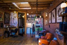 Under My Thumb Tattoo Studio. Love the aged wood flooring, raw beams, brick and skylight.