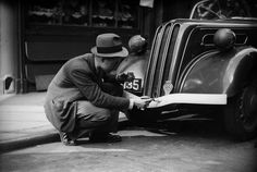 A motorist in Tudor Street, London, painting his bumpers white in accordance with blackout regulations during WWII.