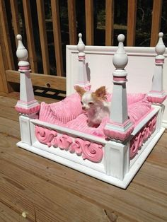 A posh princess puppy bed. This is an ornate table turned upside-down, painted, and padded, and it makes an excellent space for a dog or cat that prefers to live in the lap of luxury.
