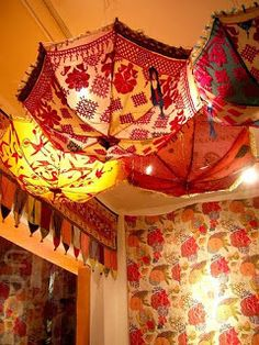 Creative lighting idea; suspending parasols from the ceiling over a lamp!