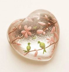 Heart shaped glass with pink blossom branches and green birds.
