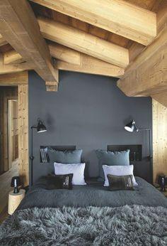 Dans la chambre sous les combles, tête de lit peinte pour alléger la forte présence du bois ; dégradé de gris, prune et mauve décliné dans le linge de lit (Caravane). Petits coussins, édition numérotée (Le Loup Philosophe) ; luminaires orientables Gras (DCW)