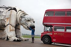 A photo of an enormous mechanical bear next to a large red bus and a woman smiling
