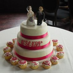 Red and white wedding cake. On top the bride and groom.
