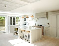 pale gray kitchen with big island and copper accents