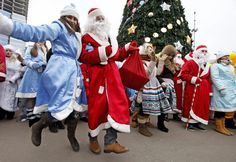"Minsk, Belarus    Men wearing Ded Moroz, ""Grandfather Frost,"" costumes join women wearing Snegurochka, ""Snow Maiden,"" costumes for the traditional march in central Minsk."
