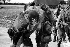 Troopers of the 82nd Airborne fitting each others parachutes