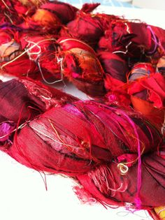 At etsy. This beautiful exhuberant red recycled sari silk ribbon is a by product from silk sari manufacturing in India. It is the waste silk sari fabric from the textile mills where they make saris.     This yarn is hand cut strips of silk sari fabric and tied together end to end and made into skeins. It is done by women's co-operatives and small businesses in India, suitable for Knitting, crochet, rug hooking, bags, wall hangings, jewellery, weaving and all sorts of fibre art projects.
