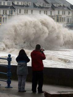 Waves crash into the Promenade at Porthcawl, South Wales