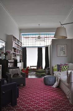 I'd like to take a nap here... I love the floor pillows and play area off of the living room. Cozy.