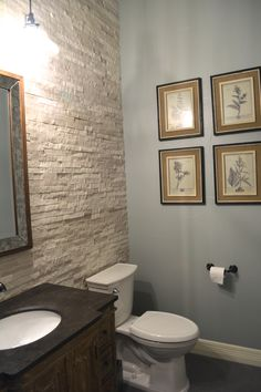 For this powder room we added new charcoal gray tile on the floor and a lighter gray stacked stone on the wall.  We painted the walls Magnetic Gray by Sherwin Williams.
