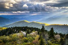 Blue Ridge Parkway scenic landscape photography showcasing some fantastic crepuscular light rays overlooking the Great Smoky Mountains National Park of Western NC. The southern Appalachians are an incredible sight during the spring bloom, offering up rich colors in the new foliage and dramatic skies as thunderstorms pass through the Blue Ridge Mountains.