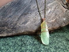 A piece of raw green calcite crystal wrapped in copper wire and strung on an 18 bronze chain*. The chain connects in the back with a clasp and