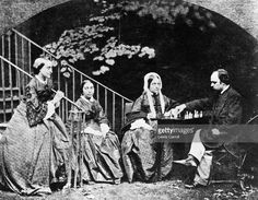 Poet and painter, Dante Gabriel Rossetti (1830 - 1894) and poet Christina Rossetti (1830 - 1894) with Maria Rossetti and their mother playing chess in the garden of Rossetti's house in Cheyne Walk, Chelsea, London. Published in The Bookman - June 1911