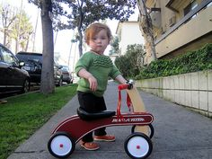 Srsly? Could she be any cuter with her ruffled retro handmade sweater and her Radio Flyer trike?