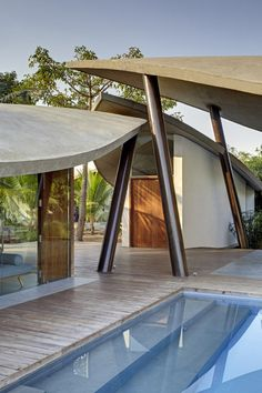 The Leaf House by SJK Architects. Utilizes concrete canopies supported by angled steel columns