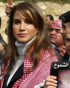 Jordanian Queen Rania holds a placard during a demonstration on 06.02.2015 in the capital Amman to express solidarity with the pilot murdered by the Islamic State (IS) group. Wearing a black suit and a red-and-white checked keffiyeh over her shoulders