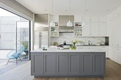 The Victorian also has a gray island in the kitchen, that contrast with the stark white wall cabinets. The gray exterior paint, and the island paint are the same color: C2's Titanium, but with different percentages. White Shaker Kitchen Cabinets, Grey Kitchen Island, Shaker Style Cabinets, Gray And White Kitchen, Shaker Style Kitchens, Kitchen Cabinet Styles, Grey Kitchens, White Cabinets, Gray Island