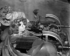 Gals of steel: American female workers, building aircraft for the war effort, check bomber machine gun turret.
