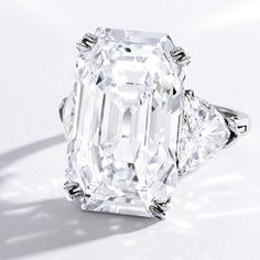 large center stone, accent diamonds, delicate band. No halo diamonds. Sits low/flat on the hand.