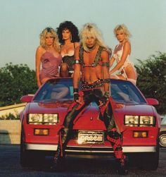 Vince Neil with Beth Lynn and some other heavy metal groupies stacked in his car. Like, how many headlights do you need?
