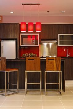 The couple%u2019s home has a multipurpose kitchen and dining area to make more efficient use of space. The dark wood island may be used as a dining table, kitchen counter, bar, and storage area.