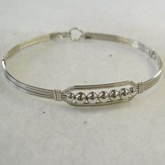 A contemporary little bracelet of five strands of sterling silver wire with a center design featuring five 4mm smooth sterling silver beads and accented with two smaller beads. Perfect to wear every day. The sturdy built-in hook and eye clasp is easy to get on and off by yourself. This bracelet is for a large wrist, measuring about 7-3/4 (19.7 cm) around.