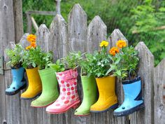 Cute and colorful planters! Use inexpensive rain boots: poke small holes through the sole for drainage, fill them with soil and your favorite plants, and hang them on your garden's fence. #gardening #diy