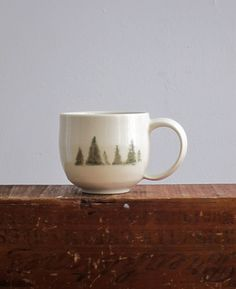 Winter pine trees are hand painted on a creamy white hand-thrown porcelain mug. Mug size and tree painting varies from mug to mug - each is one of a