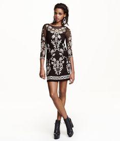 Kurzes, figurbetontes Kleid aus Mesh mit Stickereien. Das Kleid hat 3/4-Arm und ein eingenähtes Jersey-Unterkleid mit schmalen Trägern.