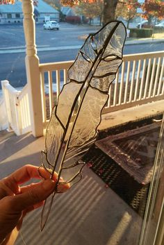 Stained glass feather suncatcher, created from art glass of various styles and textures of clear glass throughout. This piece measures 12 x 3. (Larger than most on the market.) A sturdy wire ring is embedded at the top, and strong, clear fishing line is added for either temporary or