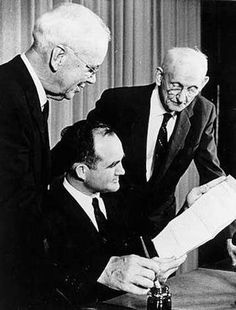 Governor John Patterson (seated) signed a bill on October 30, 1959, changing the name of the Alabama Polytechnic Institute to Auburn University.  The change became effective on January 1, 1960.  Auburn President Ralph B. Draughon (left) and Trustee Paul S. Haley witnessed the signing.