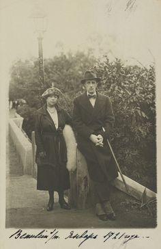 Cartão postal Príncipe Gabriel Constantinovich e sua esposa Antonina Nesterovskaya em cerca de 1921. Príncipe Gabriel está encostado a um pilar, as mãos juntas e uma bengala enganchada no braço esquerdo. Ele está vestindo um casaco, gravata borboleta e chapéu. Antonina Nesterovskaya está de pé ao lado dele à esquerda, vestindo um chapéu com uma pena e um véu e uma estola de pele. Há um poste de luz e árvores atrás deles. Em 1917 ele se casou com Antonina Nesterovskaya em uma cerimônia…