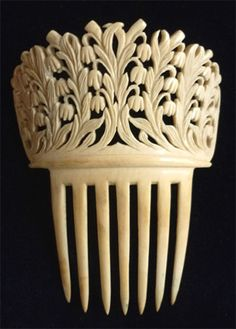 Victorian ivory comb with carved lilies of the valley in a swirl pattern that meets in the middle. English, c. 1850