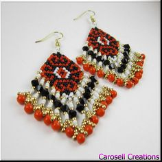 Native American style fringe seed beaded earrings. A beautiful mix of red, black, white and gold color design accentuates the stylish mood of these earrings. Each and every glass seed bead is stitched one by one using the brick stitch weaving method. The main piece is a very elegant diamond shape with each strand finished off with a loop and a single 4mm red bead. A very elegant pattern inside a diamond shape base. So much fun to show off and share! Pierced earrings come with a clear plastic…