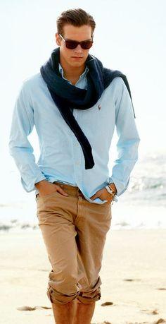 Shop this look on Lookastic:  http://lookastic.com/men/looks/cable-sweater-long-sleeve-shirt-jeans-sunglasses-bracelet/11390  — Dark Brown Sunglasses  — Navy Cable Sweater  — Light Blue Long Sleeve Shirt  — White Bracelet  — Khaki Jeans