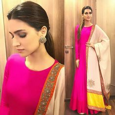 Kriti Sanon in Vasavi Wearing a hot pink long sleeve Anarkali by Vasavi, she teamed it with a contrasting cream embroidered dupatta with pops of yellow and orange. Gold studs by Satyani Jewels and a center-parted low ponytail rounded her look out. Indian Gowns, Indian Attire, Indian Wear, Indian Lehenga, Indian Style, Indian Ethnic, Lehenga Choli, Indian Wedding Outfits, Indian Outfits