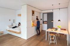 Un studio blanc et bois optimisé grâce à un meuble multifonction
