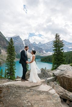 An iconic view on top of the Rock Pile at Moraine Lake, Alberta in the Canadian Rockies, after getting married on the lakeshore at a small summer destination wedding at Moraine Lake. Photo by one-edition.ca