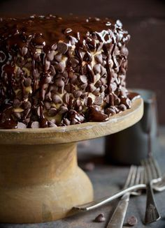 Brownie layer cake covered in cookie dough frosting with chocolate syrup drizzled over top on a rustic wooden cake stand.