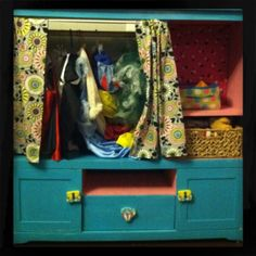 turn an old entertainment center in to a place to store toys and dress up clothes