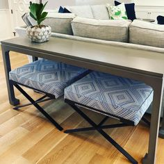Designer made the most of the unused space below a sofa console table to place a pair of Dasha metal base (shown here in a COM fabric). The ottomans can be pulled out for extra seating. Table Behind Couch, Fire Pit Table And Chairs, A Table, Living Room Storage, Living Room Seating, Living Rooms, Console Style, Modern Dining Room Tables, Hall Tables